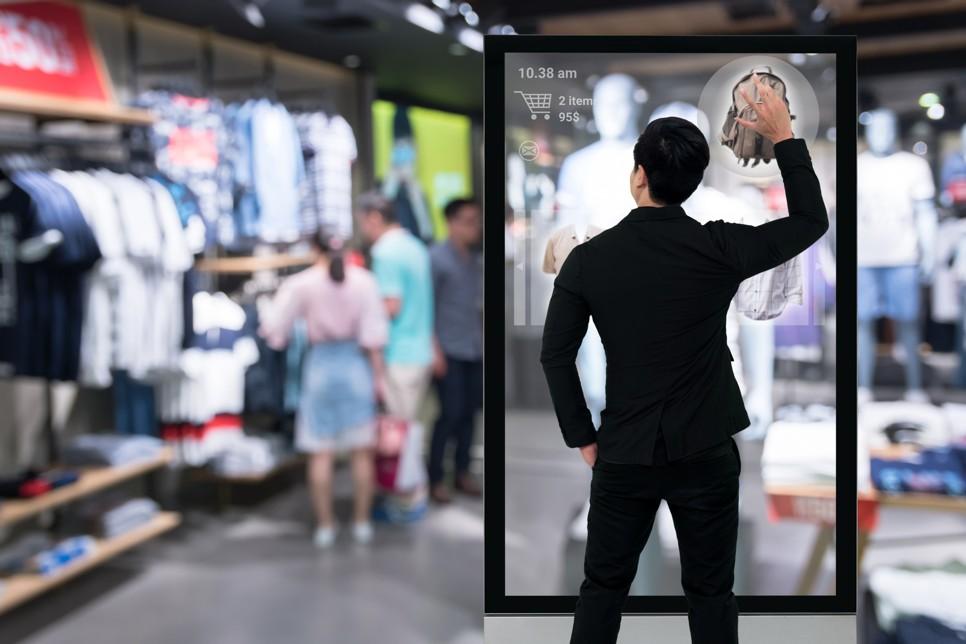 Ein Kunde benutzt eine Digital Signage Lösung am Point of Sale